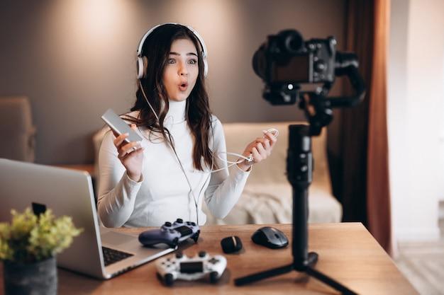 Uma bela blogueira surpresa, usando fones de ouvido, está transmitindo ao vivo falando sobre videogames. transmissão ao vivo da jovem influenciadora segura banco de energia.