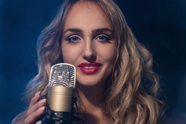 Uma bela cantora cantando no palco com a iluminação do microfone na boate