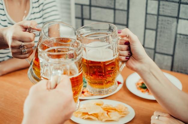 Uma bela cerveja em uma caneca segurando amigos e copos tilintar na mesa de cerveja