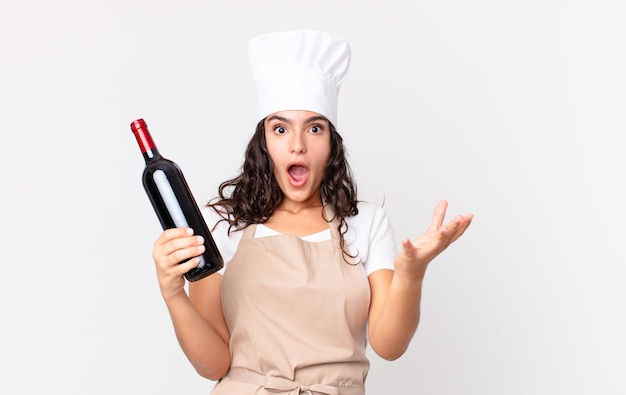 Uma bela chef hispânica se sentindo extremamente chocada e surpresa e segurando uma garrafa de vinho