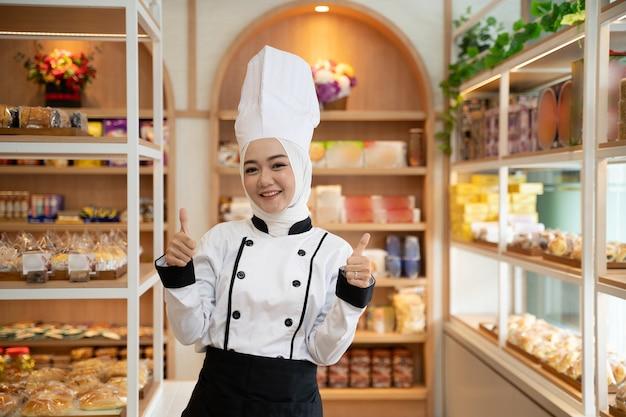 Uma bela chef muçulmana com um hijab orgulhosamente em pé em sua loja e mostrando os polegares para cima
