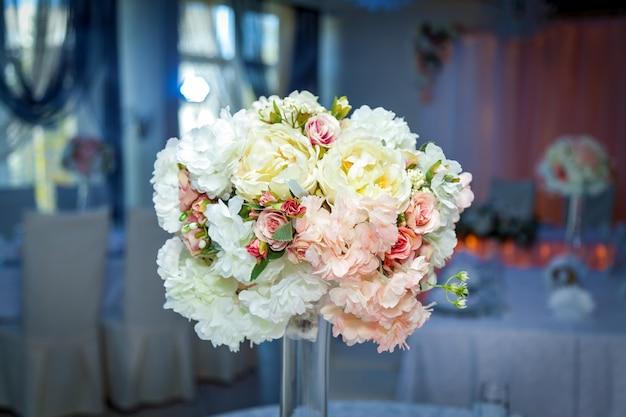 Uma bela decoração de casamento com um buquê de rosas em um vaso de vidro sobre a mesa.