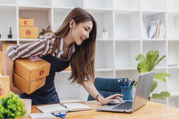 Uma bela dona de empresa asiática abre uma loja online, ela verifica os pedidos dos clientes via laptop, envia mercadorias por meio de uma empresa de courier, conceito de uma mulher abrindo um negócio online.