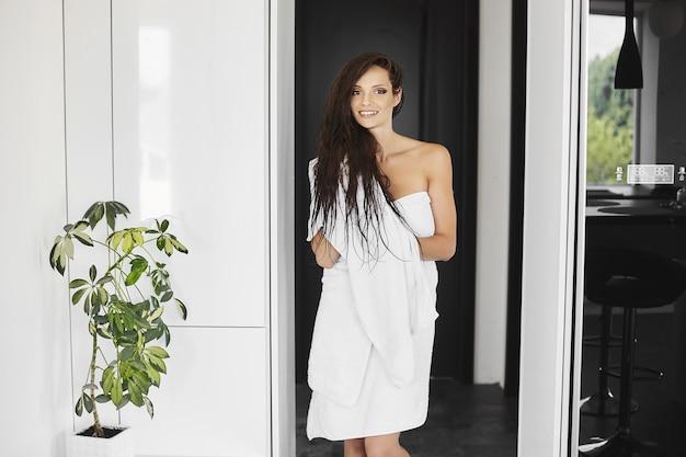 Uma bela e esguia jovem enrolada na toalha de banho posando no interior de casa o charmoso ...