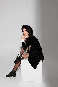 Uma bela e esguia modelo mulher em um vestido preto curto e chapéu senta-se no cubo branco no ...