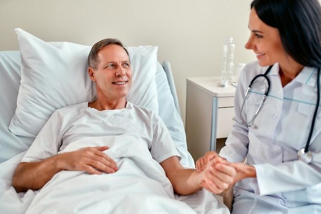 Uma bela e sorridente jovem enfermeira verifica o pulso no braço de um paciente maduro que está deitado em uma cama em uma enfermaria moderna.