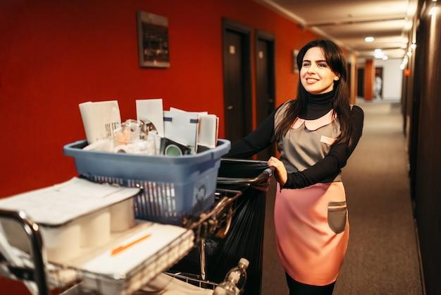 Uma bela empregada de uniforme empurra o carrinho com detergentes pelo corredor do hotel. serviço de limpeza, limpeza profissional, faxineira