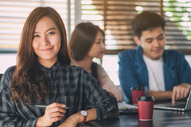 Uma bela empresária asiática com colega trabalhando no laptop no fundo