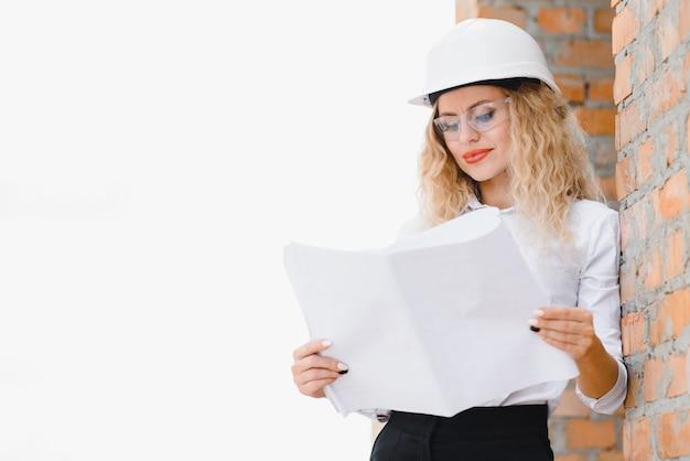 Uma bela engenheira está revisando os planos de uma obra