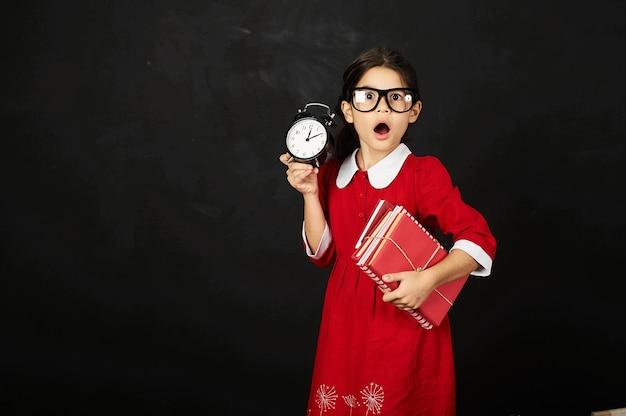 Uma bela estudante em um vestido vermelho com um livro e relógio em um fundo preto