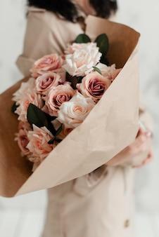 Uma bela florista tem nas mãos um lindo buquê colorido de flores decorativas feitas de rosas cor de rosa, flores brancas em um fundo de parede cinza. buquê artificial.