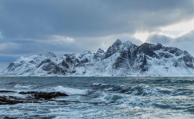 Uma bela foto das ondas do mar com uma montanha de neve ao fundo