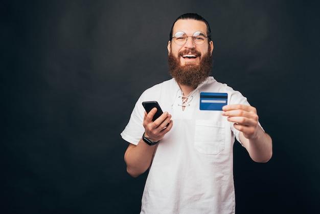 Uma bela foto de um jovem barbudo sorrindo para a câmera e segurando um telefone e um cartão de crédito pronto para fazer compras online