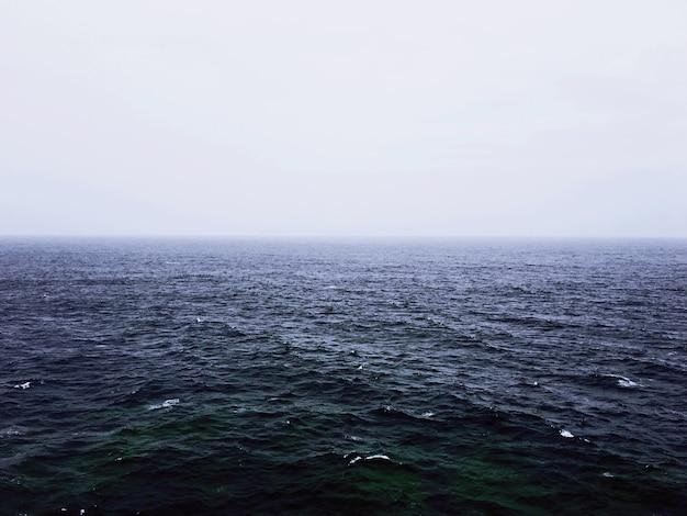 Uma bela foto de um mar vazio com um fundo nebuloso