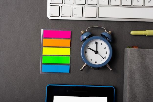 Uma bela foto de um pequeno relógio e perto dele arranjadas algumas ferramentas de escritório