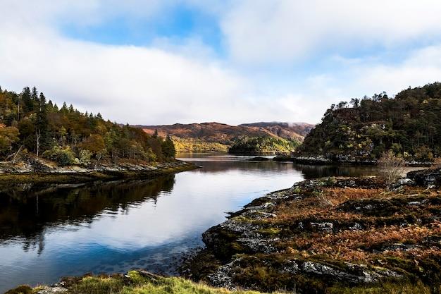 Uma bela foto de um rio no meio de montanhas arborizadas sob um céu azul nublado