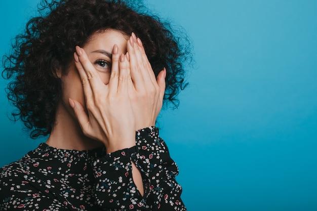 Uma bela garota com cabelo preto e encaracolado escondendo o rosto da câmera, cobrindo-o com as mãos, está posando expressivamente