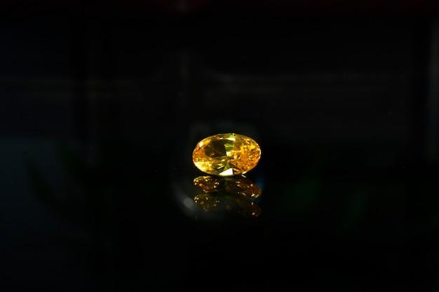 Uma bela jóia amarela sobre um piso de vidro reflexivo.