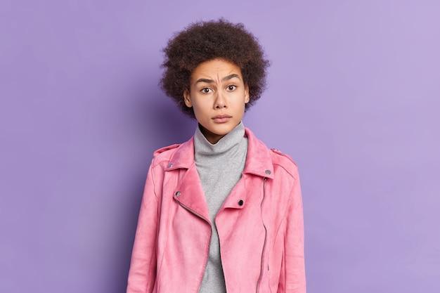 Uma bela jovem afro-americana perplexa com uma jaqueta rosa da moda reage a algo com uma expressão insatisfeita