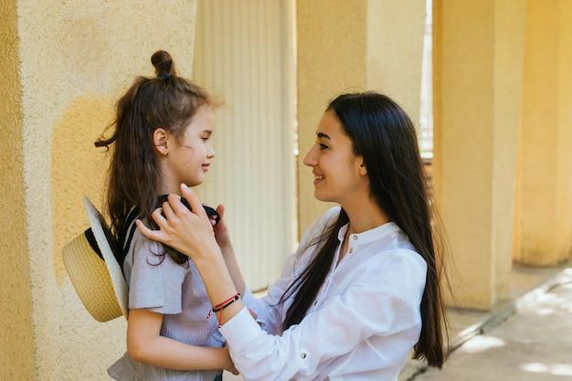 Uma bela jovem ajeita o cabelo de sua filha. lazer e recreação em família.