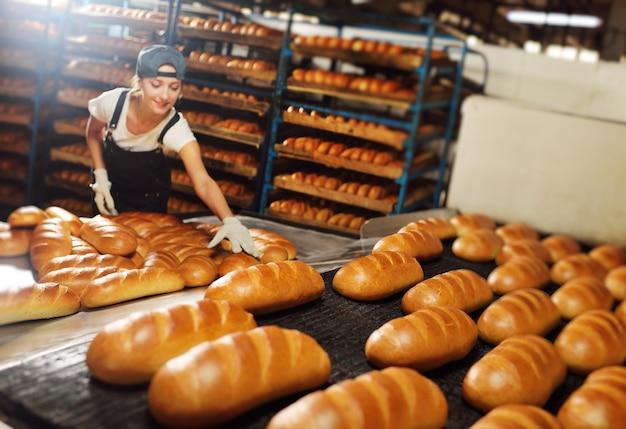 Uma bela jovem baker, de avental e boné, sorri e segura pães frescos nas mãos no contexto de uma esteira rolante com bolos em uma fábrica de pão.
