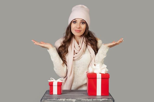 Uma bela jovem com roupas de inverno, pensativa, hesitante, fica diante da escolha de um pequeno ou grande presente para o ano novo e o natal. a menina decide qual presente escolher.