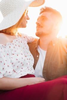 Uma bela jovem com um chapéu branco se senta no colo do marido em um campo durante uma caminhada noturna. gravidez e cuidados. felicidade e ternura. cuidado e atenção. amor e esperança .