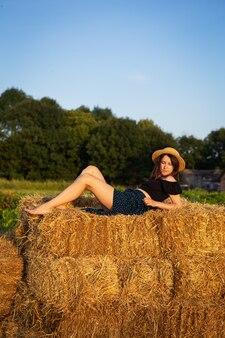 Uma bela jovem com um chapéu de palha deitada em uma grande pilha de fardos de palha