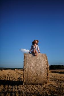 Uma bela jovem com um chapéu e um vestido de verão senta-se em um feixe de feno em um campo. natureza rural, campo de trigo