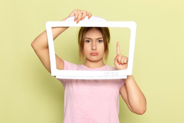 Uma bela jovem com uma camiseta rosa posando com um papel branco em forma de tv com uma expressão descontente no verde