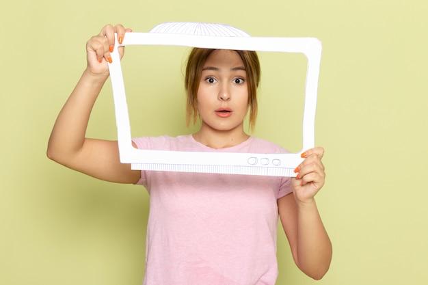 Uma bela jovem com uma camiseta rosa posando com uma tevê branca em um papel verde