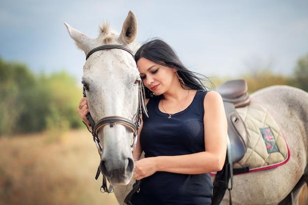 Uma bela jovem de cabelo preto abraça um cavalo. comunicação com animais