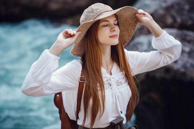 Uma bela jovem de cabelo ruivo, com um chapéu e uma mochila perto de um rio barulhento na floresta.