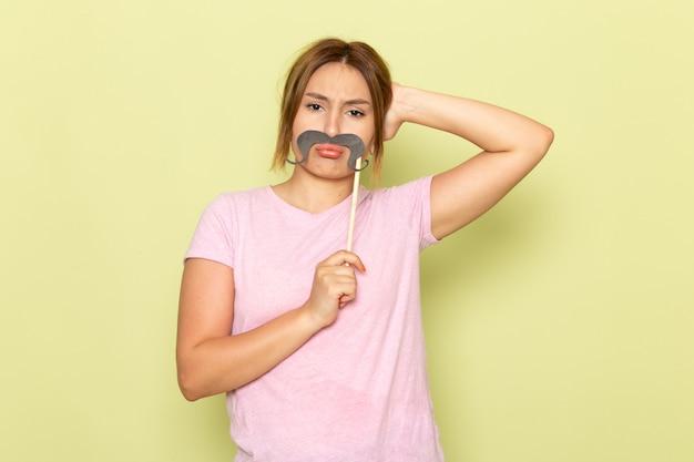 Uma bela jovem de frente para uma linda garota em uma camiseta rosa jeans posando com bigode falso e triste no verde