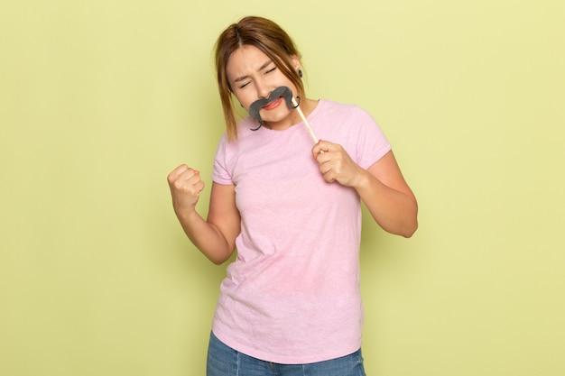 Uma bela jovem de frente para uma linda garota em uma camiseta rosa jeans posando com bigode falso em verde