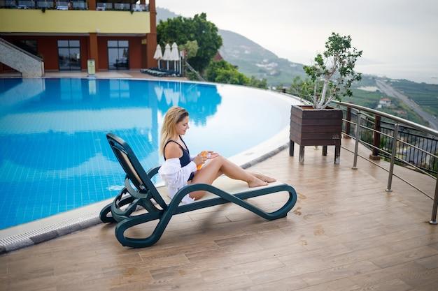 Uma bela jovem de maiô e camisa branca senta-se em uma espreguiçadeira à beira da piscina e esfrega o corpo com protetor solar. cuidados com a pele no verão, proteção contra queimaduras na pele