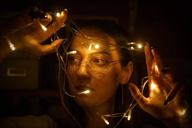 Uma bela jovem de óculos redondos, sorrindo e segurando guirlandas de luzes nas mãos.