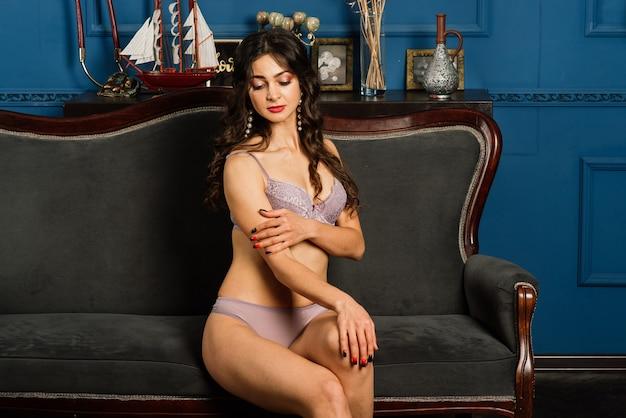 Uma bela jovem de roupa íntima está sentada na cama meio virada. o conceito da manhã da noiva.