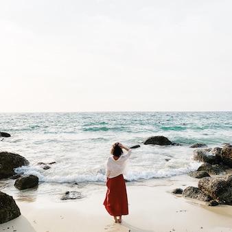 Uma bela jovem de saia vermelha e camisa branca em pé na praia observando o mar azul com ondas, pedras e céu creme
