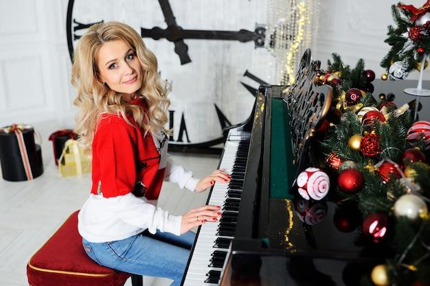 Uma bela jovem de suéter de natal toca piano e sorri contra um grande relógio e decoração de natal.
