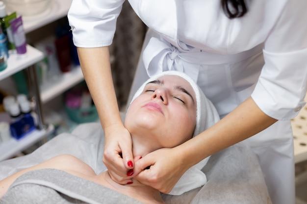 Uma bela jovem deita-se na mesa da esteticista e recebe procedimentos, uma leve massagem facial com óleo.