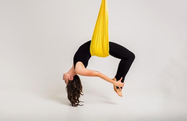 Uma bela jovem desportista realiza a pose de dhanurasana em uma rede amarela em uma parede branca com espaço para texto