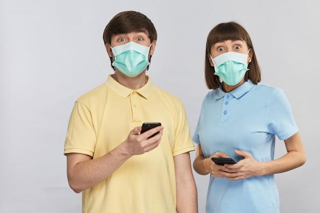 Uma bela jovem e um homem de camisas amarelas e azuis segurando smartphones e, surpreso, olhando para a câmera com olhos grandes em máscaras de proteção, copie o espaço