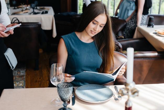 Uma bela jovem em um restaurante elegante olha o cardápio e faz um pedido para um jovem garçom com um avental estiloso. atendimento ao cliente.