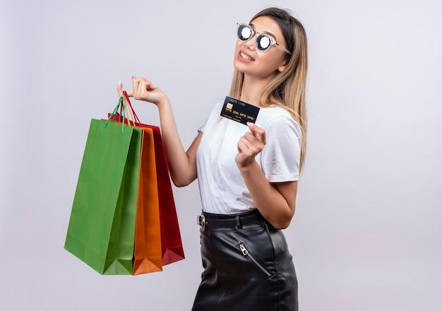 Uma bela jovem em uma camiseta branca usando óculos escuros, mostrando o cartão de crédito, segurando sacolas de compras em uma parede branca
