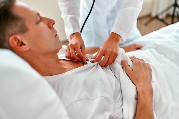 Uma bela jovem enfermeira com um estetoscópio examina um paciente maduro que está deitado em uma cama em uma enfermaria moderna.