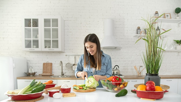 Uma bela jovem está preparando uma salada de vários vegetais na cozinha.