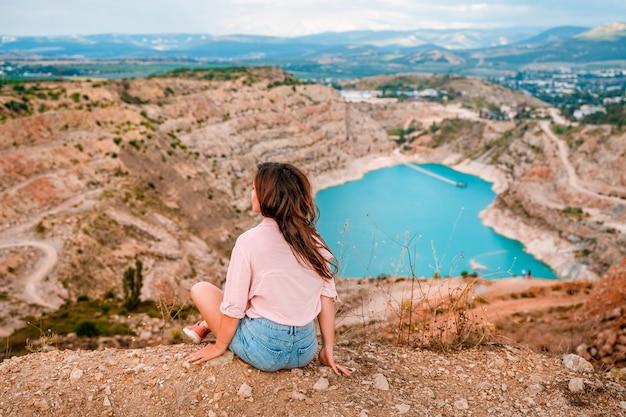 Uma bela jovem está sentada na beira de um penhasco com uma pedreira em forma de coração