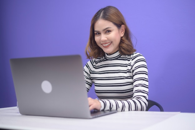Uma bela jovem está trabalhando com seu computador sobre fundo azul.