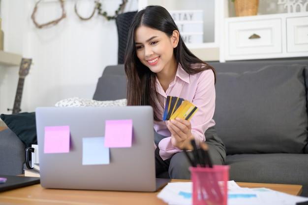 Uma bela jovem está usando cartão de crédito para fazer compras on-line em um site da internet em casa, conceito de comércio eletrônico